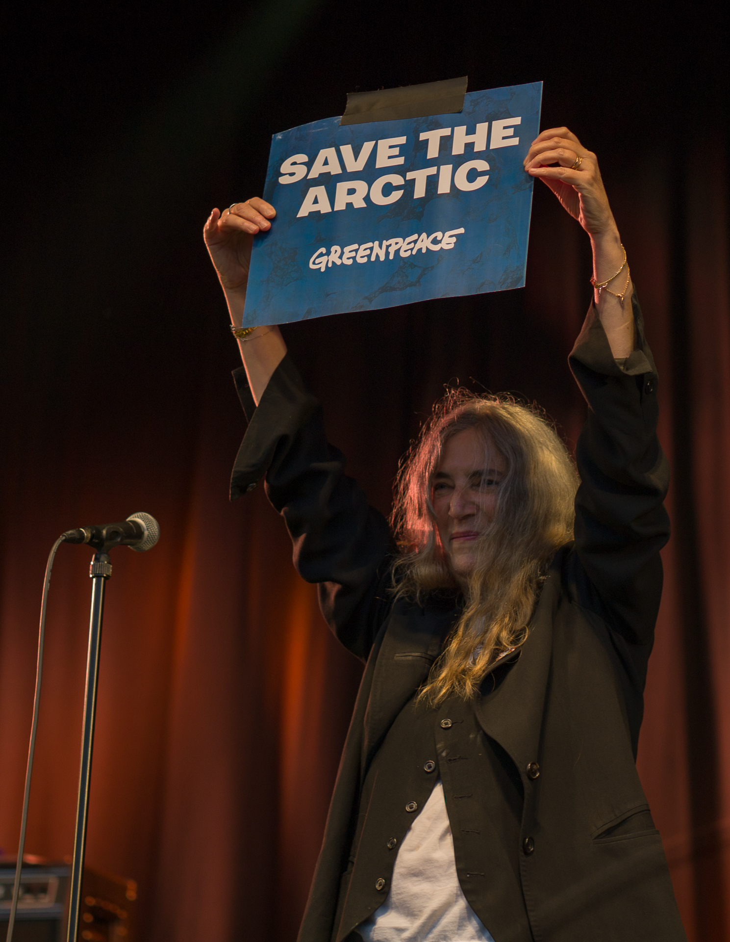Patti Smith holding sign Magnus