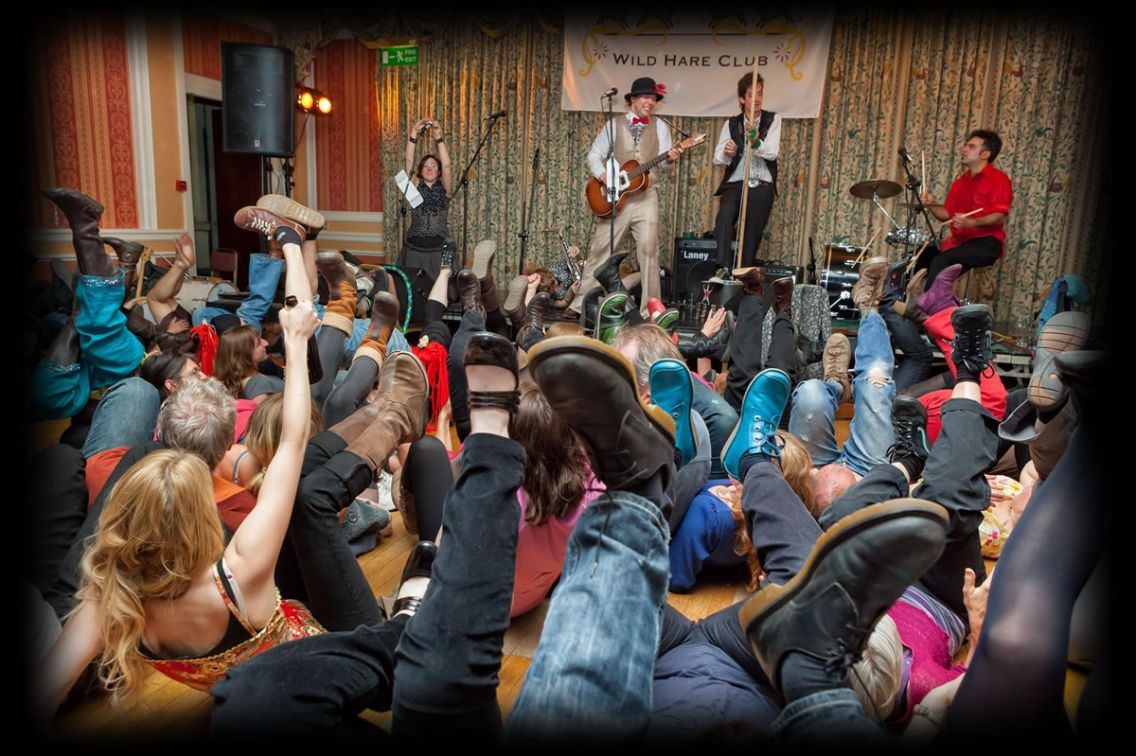 Blackberry Wood in front of the Wildh Hare Club banner with the audience all lying on the floor waving their legs in the air with wild abandon
