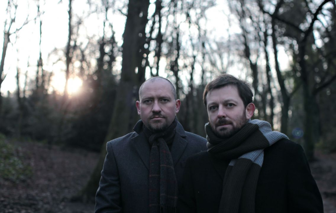 Richard Oakes and Sean McGhee in frot of woods as the sun goes down