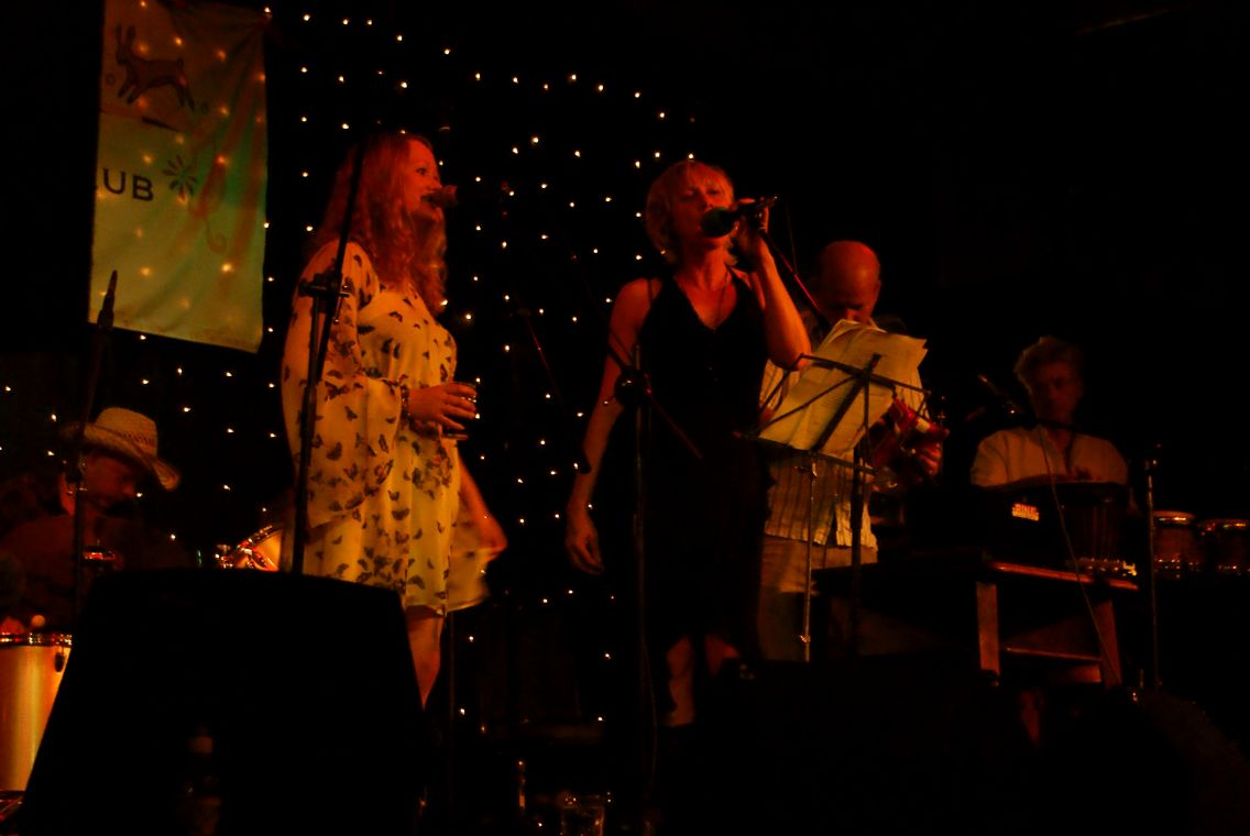 Sarah & Kate of Sproatly Smith singing with backdrop of fairy lights