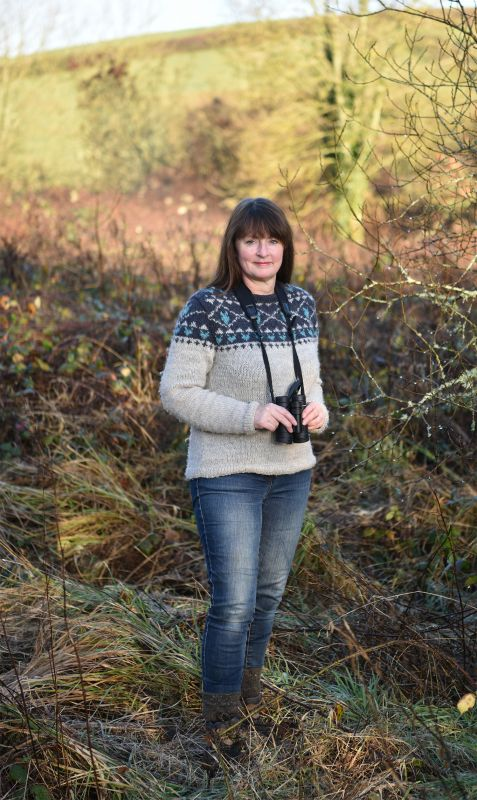 Miriam Darlinton in the field with a pair of binoculars slung around her neck and a lovely knitted jumper